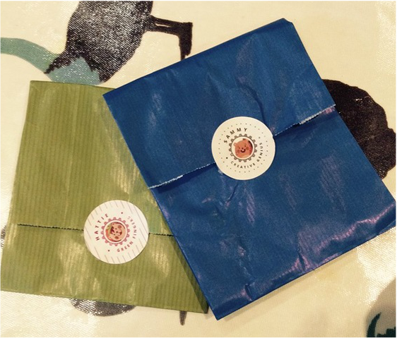 Two small paper packages in green and blue.