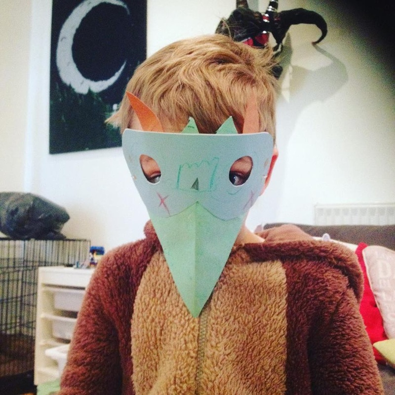 A boy is wearing a bird mask he made.